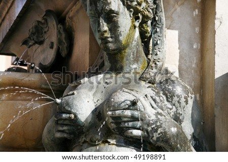 Detail of famous Fountain of Neptune in Bologna, Italy. Close-up of lactating nereid. - stock photo