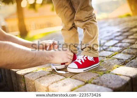 Detail of father's hands tying his little son's shoes - stock photo