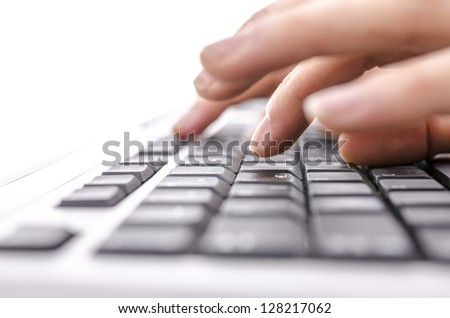 Detail of female fingers typing on keyboard. With selective focus.