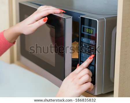 Detail of female hand while using the microwave - stock photo