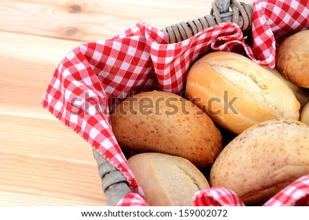 Detail of fresh bread rolls in a rustic picnic basket lined with red gingham - stock photo