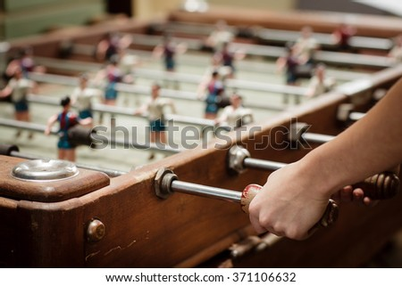 Detail of girl's hands playing the foosball vintage table match. Color toned image. Concept photo of leading the company. - stock photo
