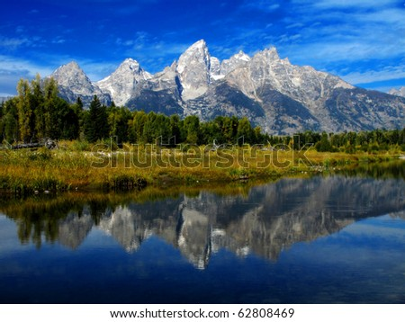 Detail of Grand Tetons Mountains with blue sky with relfection in river - stock photo