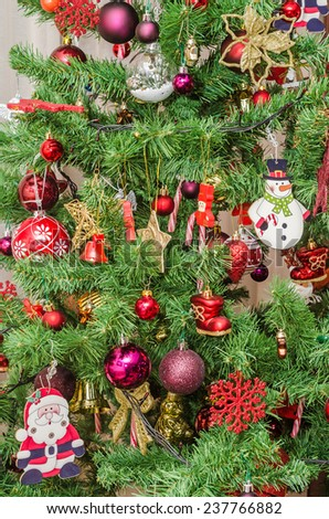 Detail of green Christmas (Chrismas) tree with colored ornaments, globes, stars, Santa Claus, Snowman, red boots, shoes, candles, bells, white transparent angels, snow flakes and candy sticks - stock photo
