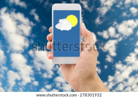 Detail of hand consulting the prediction weather with the smartphone with clouds and sky in background. All screen content is designed by me and not copyrighted by others and created  - stock photo