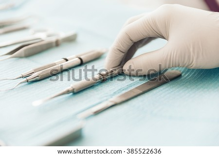 Detail of hand holding dental tools in dental clinic. Dentist Concept. - stock photo