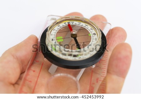 Detail of hand holding glass compass on white background - stock photo