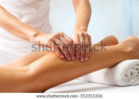 Detail of hands massaging human calf muscle.Therapist applying pressure on female leg. - stock photo