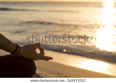 Detail of hands while meditation at the beach - stock photo