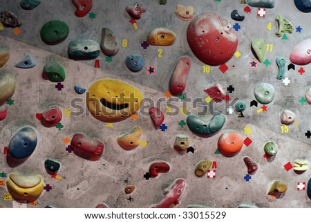 Detail of indoor climbing wall with different sized grips - stock photo