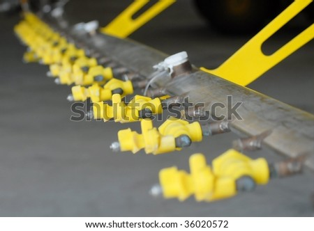 Detail of industrial agriculture crop duster sprayers. The spray nozzles are yellow.  The perspective is looking down the line of spray nozzles. Shallow depth of field focuses on the third nozzle - stock photo
