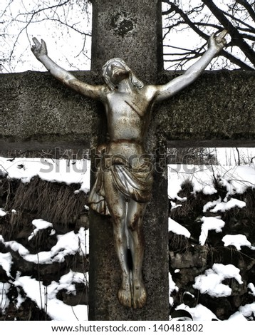 Detail of Jesus Christ on cross in winter time. Statue. - stock photo
