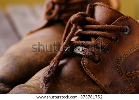 Detail of laces on old worn brown leather shoes. Boots are placed on wooden grey board in front of yellow wall. - stock photo