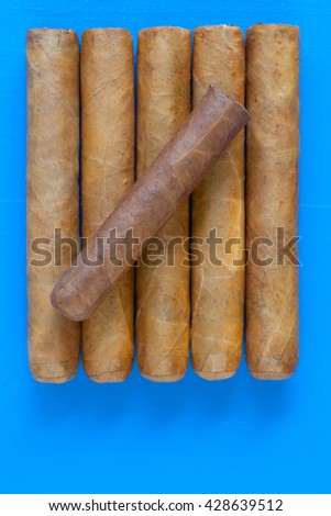 Detail of luxury Cuban cigars on the blue table - stock photo