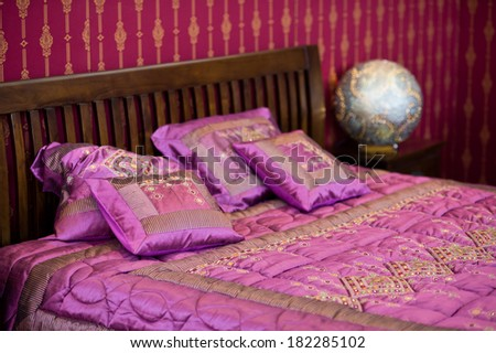Detail of magenta cushion on the bed in beautiful colored bedroom - stock photo