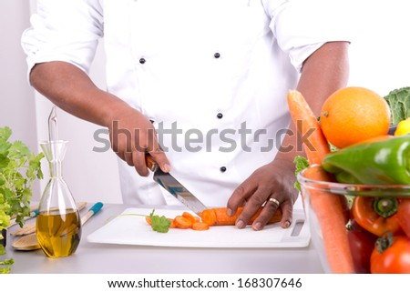Detail of male chef hands with fruits and vegetables on table - stock photo