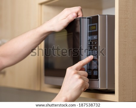 Detail of male hand while using the microwave - stock photo