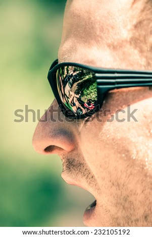 Detail of man face with open mouth wearing sport sunglasses - stock photo