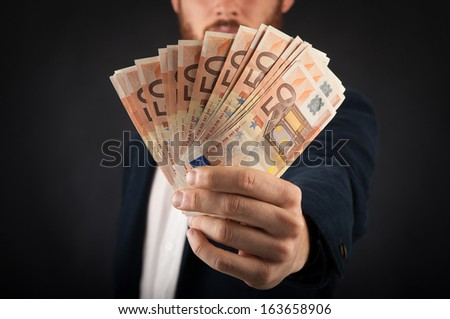Detail of man's hand showing euros banknotes against black background. - stock photo