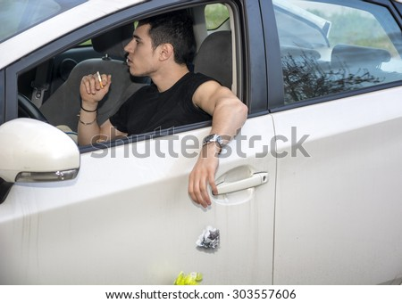Detail of Man Wearing Wrist Watch Tossing Crumpled Ball of Refuse Out of Car Window onto Ground, Close Up of Irresponsible Man Littering Garbage from Car - stock photo