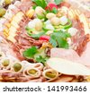 Detail of meat delicatessen plate arranged with cherry tomato, olives and parsley. - stock photo