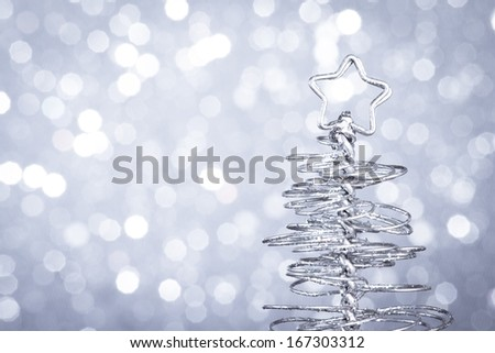 detail of metallic modern christmas tree on wood table on silver tint light bokeh background with space for text - stock photo