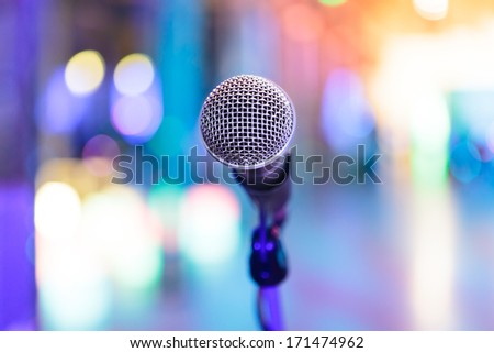 Detail of microphone with bright blurred party lights around - stock photo