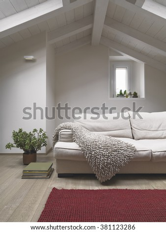 detail of modern fabric sofa in the  living room in the penthouse with wood ceiling and wood floor - stock photo