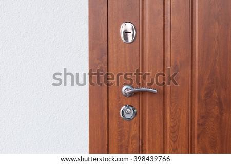 Detail of Modern style metallic door handle on wooden door - stock photo