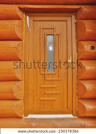 Detail of new built door built in wooden beams cabin wall. Painted wood with fungicide light red paint.  - stock photo