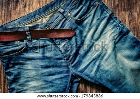 Detail of nice blue jeans with leather belt in vintage style - stock photo