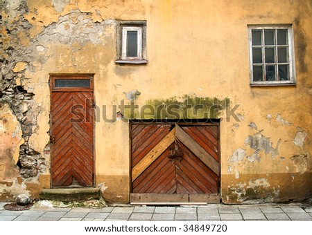 Detail of old building facade with arch doors and windows in a town. - stock photo