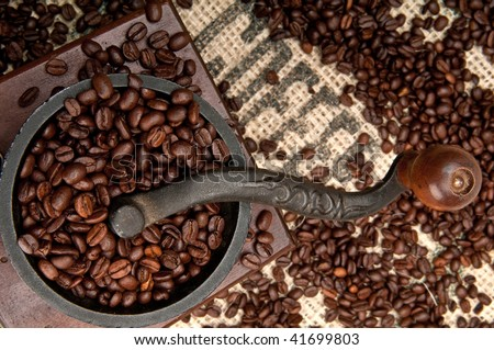 Detail of Old Coffee Grinder and beans with Burlap. - stock photo