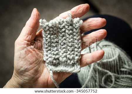 Detail of old hand holding the peace of knitting texture.