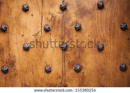 Detail of old solid door. Wood and metal door with metallic spikes looking worn and grungy. Part of ancient castle or fortress. Abstract backgrounds and wallpapers. - stock photo