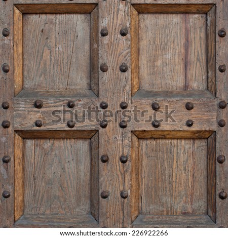 Detail of old solid door. Wood and metal door with metallic spikes looking worn and grungy. Part of ancient castle or fortress.  - stock photo