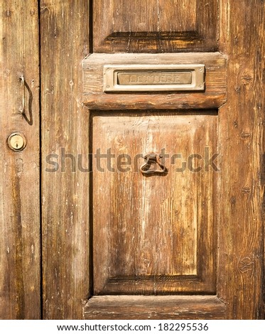 detail of old wood door with postbox for background - stock photo