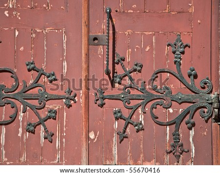 Detail of old wooden door with wrought iron handle. Close-up detail of the architecture. - stock photo