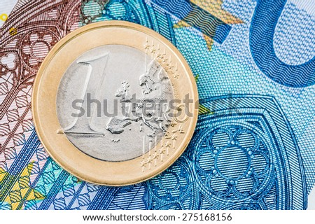 Detail of one Euro coin on blue banknote background - stock photo