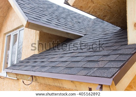 Detail of overlapping roofing tiles on a new build wooden house with dormer windows - stock photo