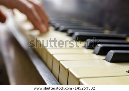 Detail of pianist hand playing vintage piano. - stock photo