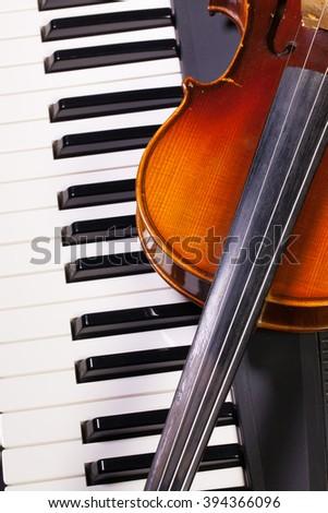 Detail of piano keyboard and old violin - stock photo
