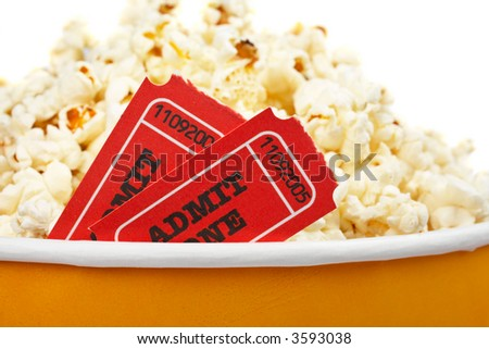 Detail of popcorn in a bucket and two tickets over a white background. Tickets on focus and shallow DOF - stock photo