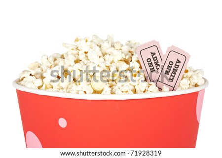 Detail of popcorn in a bucket and two tickets over a white background. Tickets on focus and shallow depth of field - stock photo