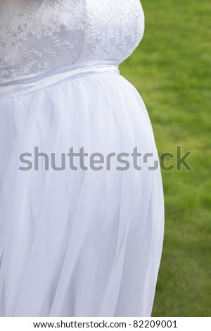 Detail of pregnant bride's belly in a wedding dress