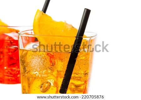 detail of red and yellow cocktail with orange slice on top and straw isolated on white background with space for text - stock photo