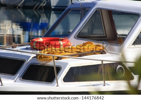 detail of red float tied to a small rope on boat deck - stock photo