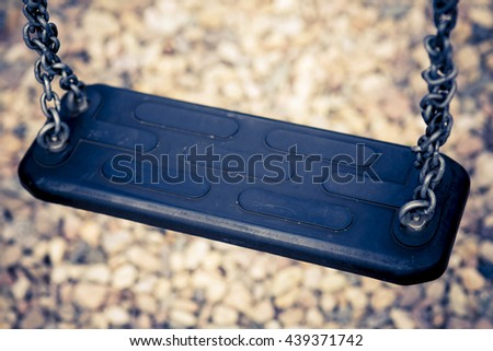 detail of seat from black children swing with chain - stock photo