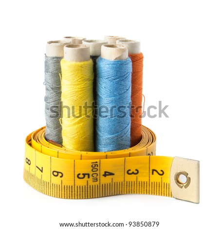 Detail of sewing thread with measure tape isolated on white background - stock photo