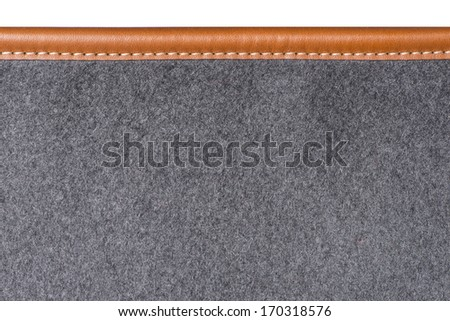 detail of sewn beige leather binding on grey rug - stock photo